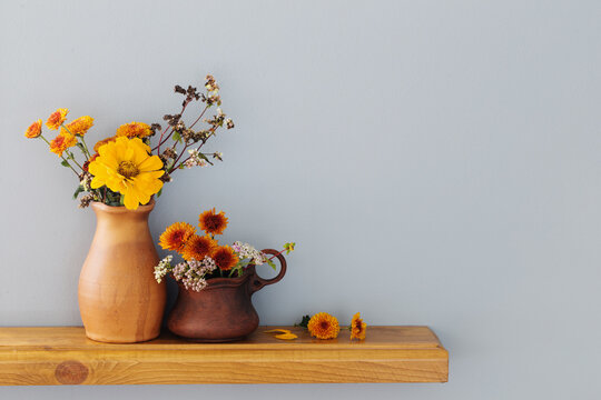 autumn flowers in rustic ceramic vase on background gray wall