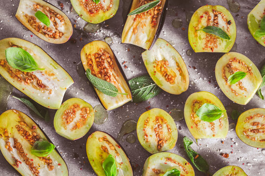 Small raw eggplants prepared for baking on baking sheet