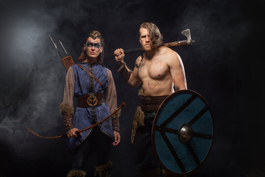 Man and woman warriors in battle with bow and ax. Ancient times. Fantasy concept