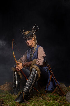 Beautiful female viking woman warrior in battle with bow. Ancient times. Amazon fantasy girl