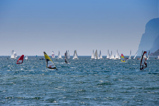 Windsurfer surfing and sailboats sailing the wind on waves In lake Lago di Garda