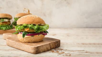 Fototapeta Wooden board with tasty vegetarian burger on table obraz
