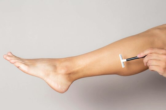 female hand shaves leg with disposable razor on white background