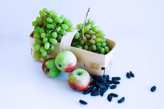 grapes in a wicker basket next to apples and raisins on a white background