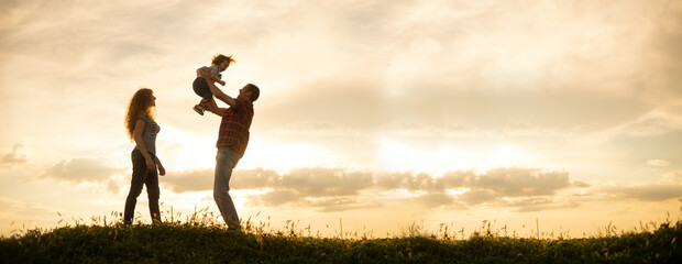 Caucasian family mom dad and little son at sunset. Silhouettes of parents and toddler boy on the background of the sky Freedom and an active lifestyle