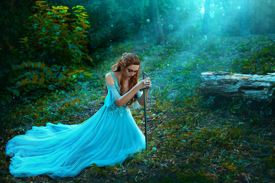 Fantasy elf woman princess warrior sits in forest on green grass holding weapon medieval sword in hands. Warlike queen red haired girl in blue medieval dress. Trees divine sun rays blessing light fog