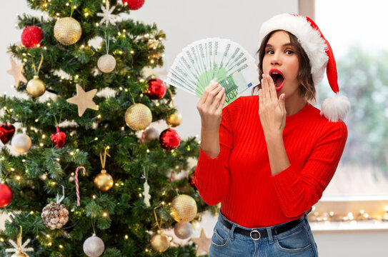 winter holidays and finance concept - surprised young woman in santa helper hat holding euro money banknotes over christmas tree on background