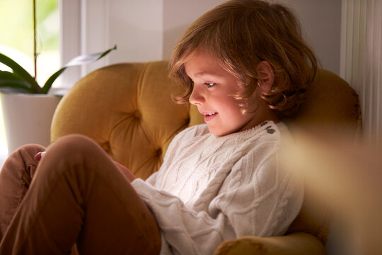 Smiling Boy With Face Illuminated By Screen Of Phone Playing Game At Home