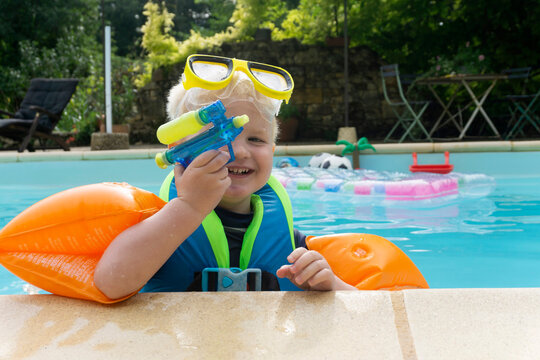 A cute young boy wearing arm bands and goggles playing with a water pistol in a swimming pool