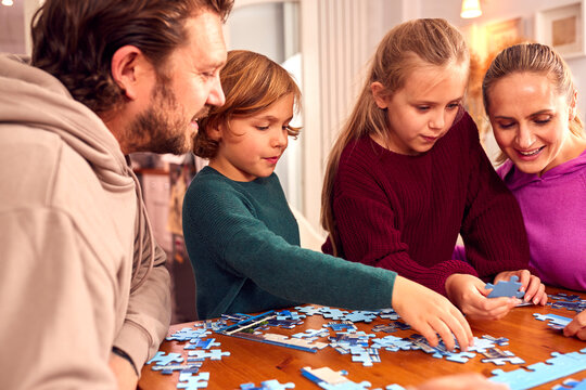 Family Sitting Around Table At Home Doing Jigsaw Puzzle Together