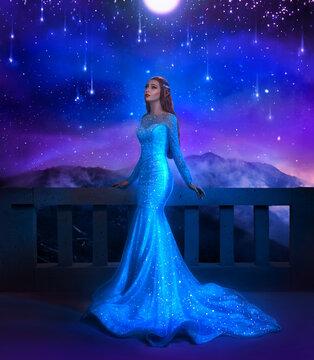Fantasy woman princess stands on balcony looks at night sky space cosmos stars. Girl enjoy magic starfall ball. Elegant long shiny blue dress. Character cosplay book ACOTAR Fairy Queen Feyre Archeron