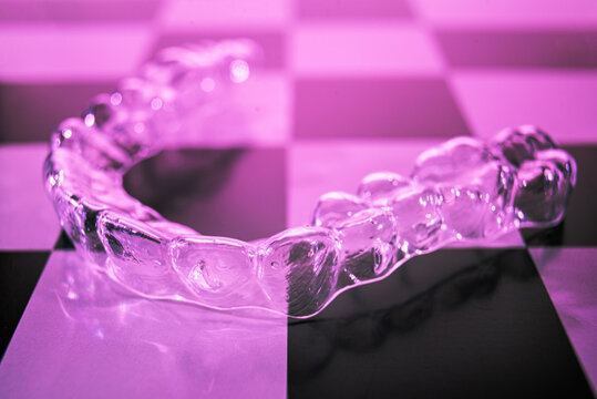 Invisible dental braces lie on a checkerboard. Plastic braces dentistry retainers to straighten teeth.