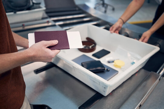 Passenger holding passport against personal Items, liquids, and laptop in container at airport security check..