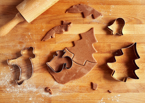 Cutting out shapes from dough for gingerbread Christmas cookies