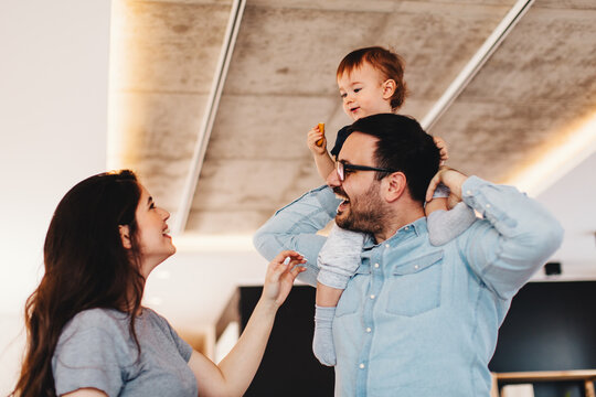 Young father holding the son on their shoulders  at home and laughing with mom next to them