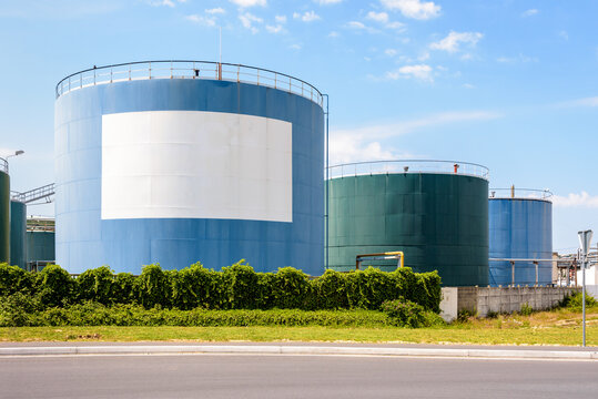 Large coloured storage tanks for oil and fuel in a tank farm with a white blank copy space under a blue sky.