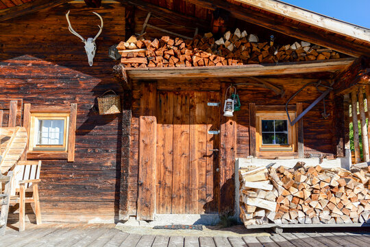 Entrance door to old wooden cabin or blockhouse with firewood for heating at mountain meadow in the austrian alps, Zillertal Austria