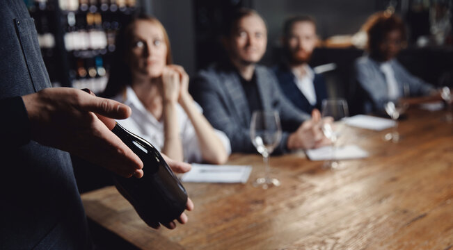 Banner Male sommelier conducts red wine tasting for restaurant guests
