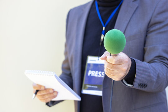 Correspondent holding microphone making media interview