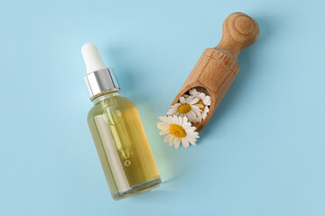 Fototapeta Bottle of essential oil and scoop with chamomile flowers on color background obraz