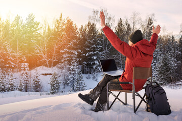 Fototapeta Adult man blogger or freelancer working on a laptop in winter forest. Freedom, remote work concept. obraz