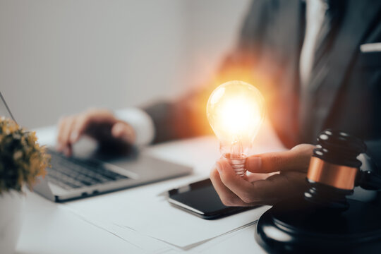Male lawyer is shown working in an office with a businessman who is holding a light bulb. Concepts of legal law, counsel, and justice, as well as the idea of a lawyer.