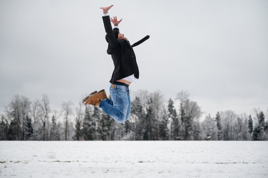 Cheerful man jumping in the air outside in winter nature