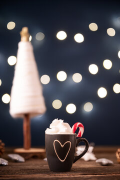 Small cup of hot chocolate with heaping whipped cream decorated with sugar candy cane