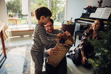 Obraz Family opening Christmas gifts together - fototapety do salonu