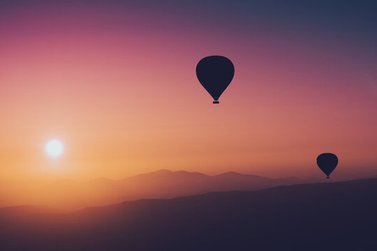 hot air balloon silhouettes with sun rising over the mountains