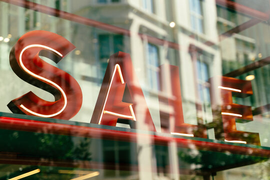 sale sign in shop window with reflections