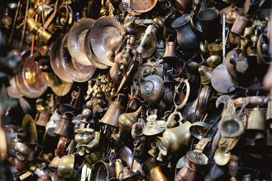 antique metallic pots and plates hanging on a wall