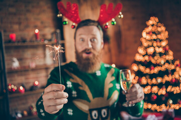 Fototapeta Photo of crazy funny funky guy hold glass champagne bengal fire wear reindeer headband jumper decorated home indoors obraz