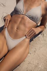 Fototapeta Woman with perfect body in bikini on sandy beach, closeup obraz