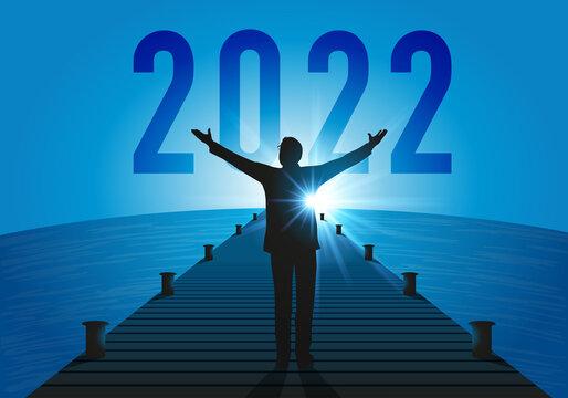 Carte de vœux 2022 sous le signe de l'espoir, avec un homme d'affaire optimiste, qui lève les bras vers une nouvelle année qui annonce une reprise économique.