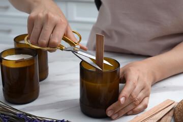 Fototapeta Woman cutting wick of homemade candle at table indoors, closeup obraz