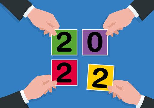 Carte de vœux sous le signe du partenariat et de l'union des compétences, avec le symbole de 4 mains tenant des carrés de couleurs pour former le chiffre 2022.