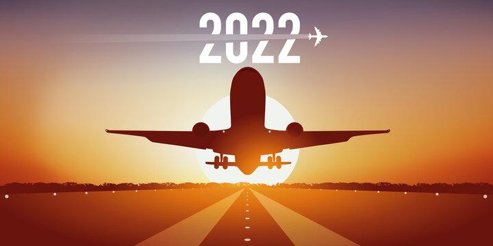 Carte de vœux 2022 pour les compagnies aériennes, montrant un avion prenant son envol, en décollant de la piste d'un aéroport devant un coucher de soleil.