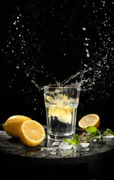 splashing lemonade with fresh lemons on black