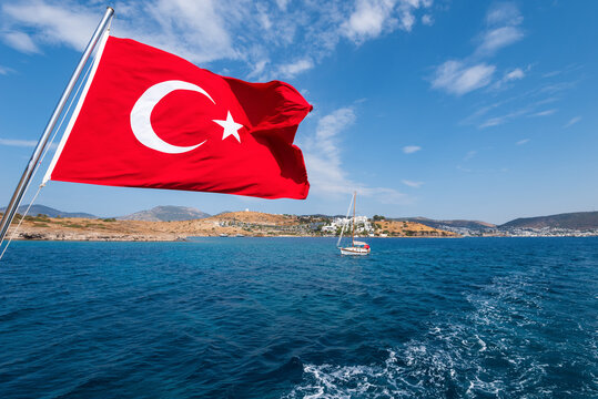 The flag of Turkey is flying on a boat over the sea