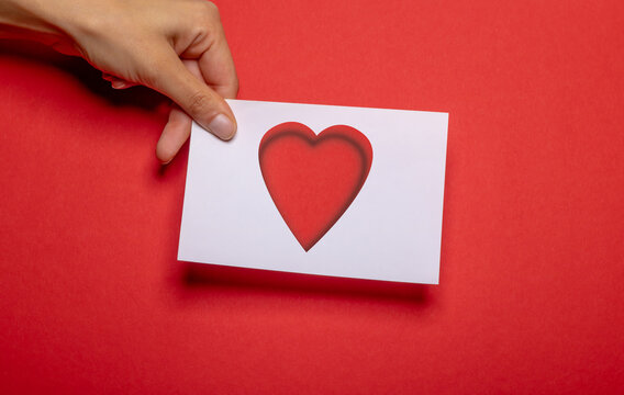 female hand holds a piece of paper paper with cut out heart shape as love symbol over strong red background cardboard