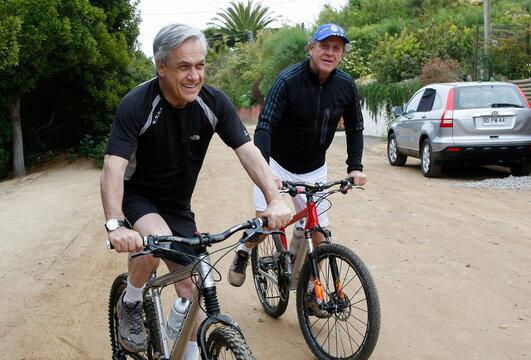 Chile's President Sebastian Pinera and his friend, businessman Carlos Alberto Delano, ride their bikes in Zapallar