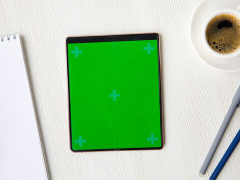 New folding Smartphone Samsung Galaxy Z Fold 2 with green screen, open notebook, cup of coffee, pens lying on white table. Flat lay top view, mock up. October 4 ,2021 Novosibirsk,Russia