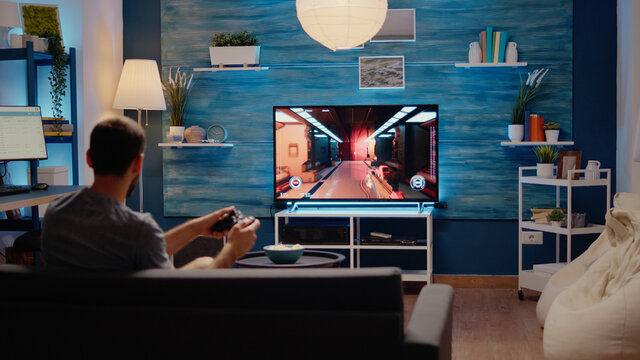 Caucasian gamer playing action games on tv console using wireless joystick with modern technology. Young man of simulator enjoyment gaming on electronic devices as hobby and leisure