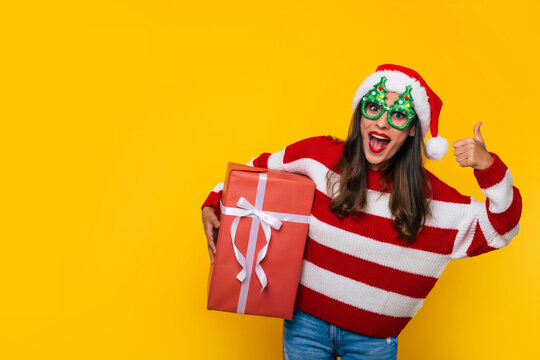 Close up photo of beautiful excited smiling woman with Christmas gift box in hands is showing thumb up while posing on yellow background