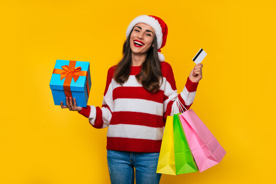 Happy stylish beautiful woman in Christmas hat with colorful shopping bags isolated on yellow background
