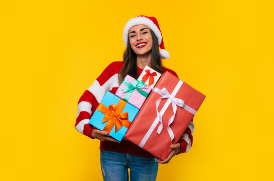 Close up photo of beautiful excited smiling woman with many cool Christmas gift boxes in hands while she is having fun and posing on yellow background