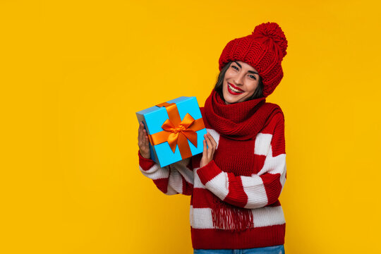 Close up photo of beautiful excited smiling woman in winter clothes with Christmas gift box in hands is having fun while posing on yellow background