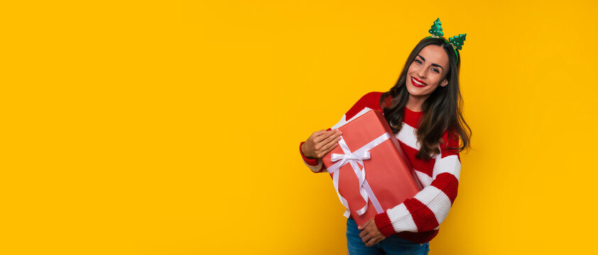 Wide banner photo of beautiful excited smiling woman with Christmas gift box in hands is having fun while posing on yellow background