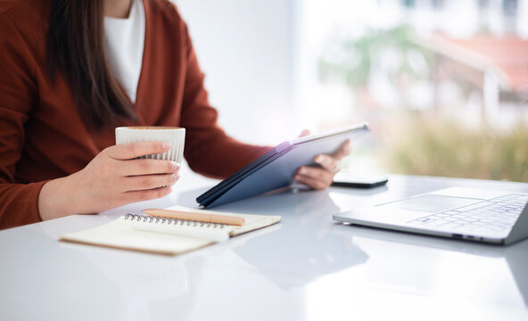 focus on hand young asian businesswoman using mobile app from digital tablet working and meeting online and other hand holding coffee cup